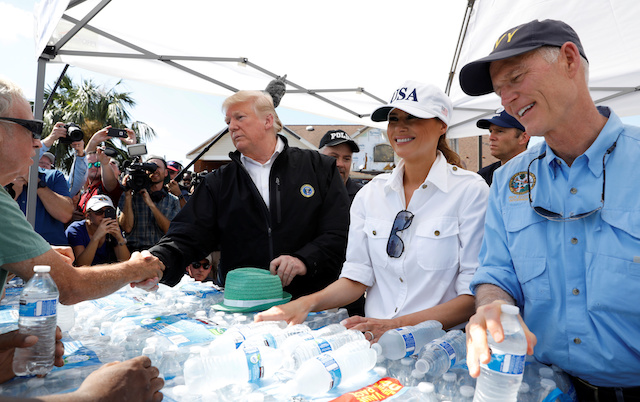U.S. President Donald Trump, first lady Melania Trump and Florida Governor Rick Scott (R) help distribute water in the town of Lynn Haven, Florida, during a tour of areas ravaged by Hurricane Michael in Florida U.S., October 15, 2018. REUTERS/Kevin Lamarque