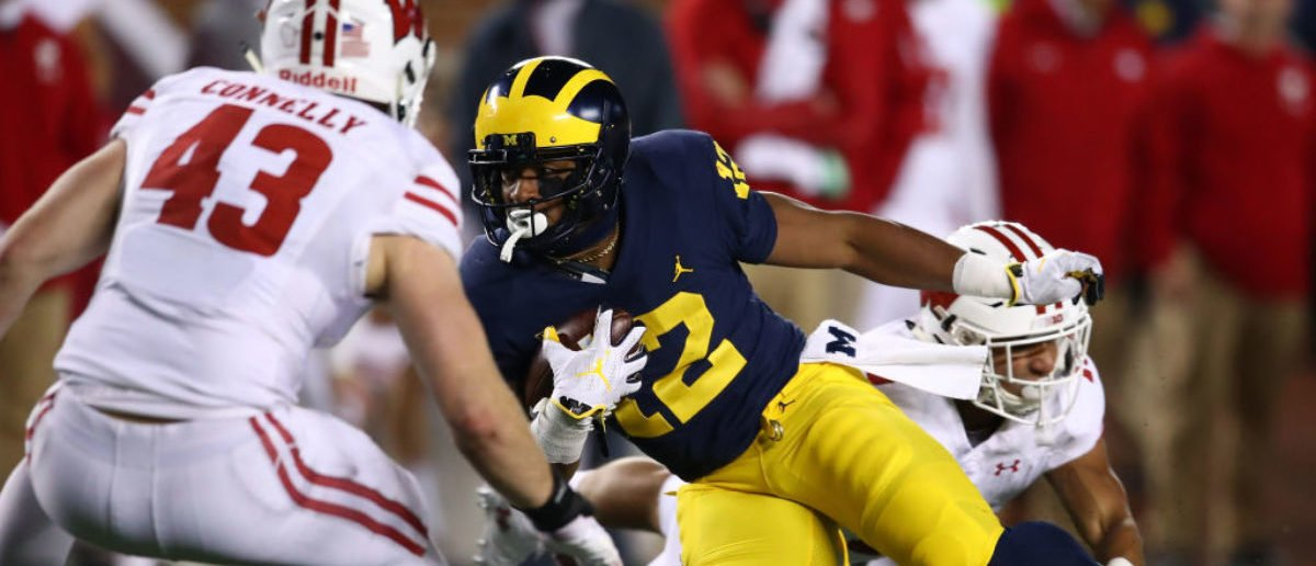 ANN ARBOR, MI - OCTOBER 13: Karan Higdon #22 of the Michigan Wolverines battles for yards between Evan Bondoc #13 and Ryan Connelly #43 of the Wisconsin Badgers on October 13, 2018 at Michigan Stadium in Ann Arbor, Michigan. Michigan won the game 38-13. (Photo by Gregory Shamus/Getty Images)