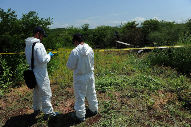 State forensic personnel work on the site where a police helicopter participating in an operation to capture leaders of an unidentified criminal group was shot down on the eve, on September 7, 2016 in El Chauz, Michoacan State, Mexico. Authorities hunted on Wednesday for gang suspects who shot down a helicopter carrying police in western Mexico, killing four aboard in a clash highlighting the government's struggle to quell violence in the region. PEDRO PARDO/AFP/Getty Images