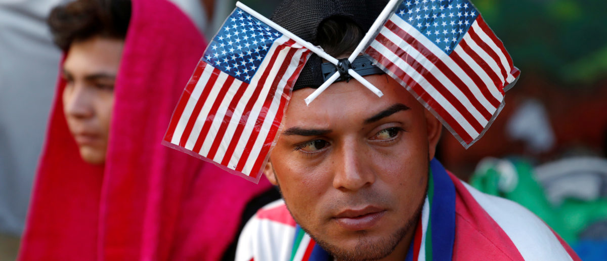 A Central American migrant, part of a caravan trying to reach the U.S., is pictured with U.S. flags on his head as he waits to reunite with more migrants, in Tecun Uman, Guatemala, October 27, 2018. REUTERS/Carlos Garcia Rawlins