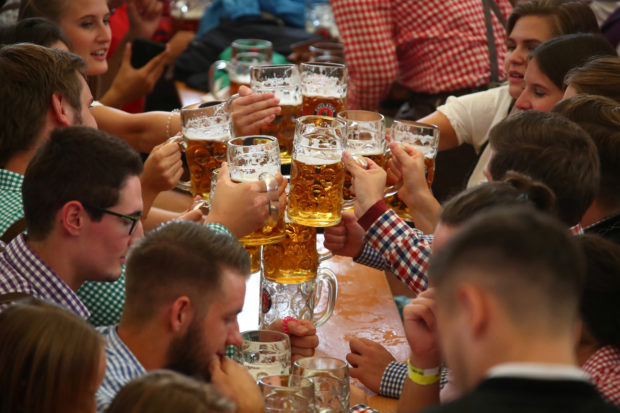 Visitors toast with beers during the opening day of the 185th Oktoberfest in Munich