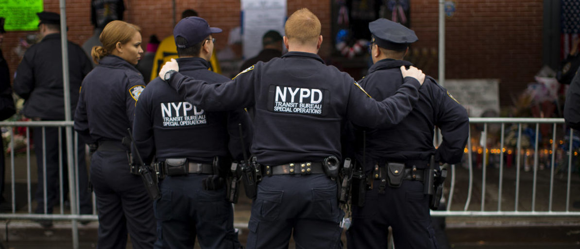 New York City Police officers pause as they visit a makeshift memorial at the site where two of their fellow police officers were fatally shot in the Brooklyn borough of New York, December 23, 2014. NYPD officers, Wenjian Liu and Rafael Ramos were shot and killed as they sat in a marked squad car in Brooklyn on Saturday afternoon, New York Police Commissioner William Bratton said. The suspect in the shooting then shot and killed himself, according to Bratton. REUTERS/Mike Segar