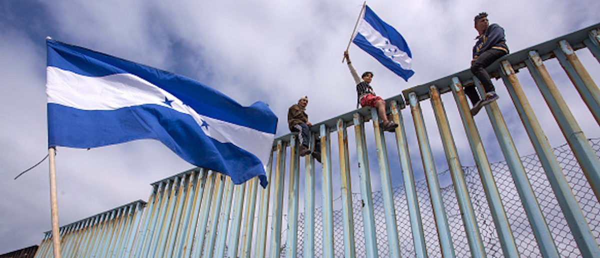TIJUANA, MEXICO - APRIL 29: People hold Honduran flags at the border fence during a rally with members of a caravan of Central American asylum seekers and supporters on April 29, 2018 in Tijuana, Baja California Norte, Mexico. More than 300 immigrants, the remnants of a caravan of Central Americans that journeyed across Mexico to ask for asylum in the United States, have reached the border to apply for legal entry. (Photo by David McNew/Getty Images)