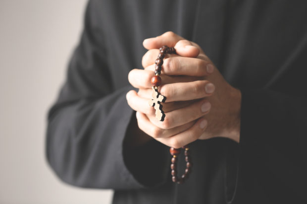 A Catholic priest carrying rosary beads (Shutterstock/Africa Studio)