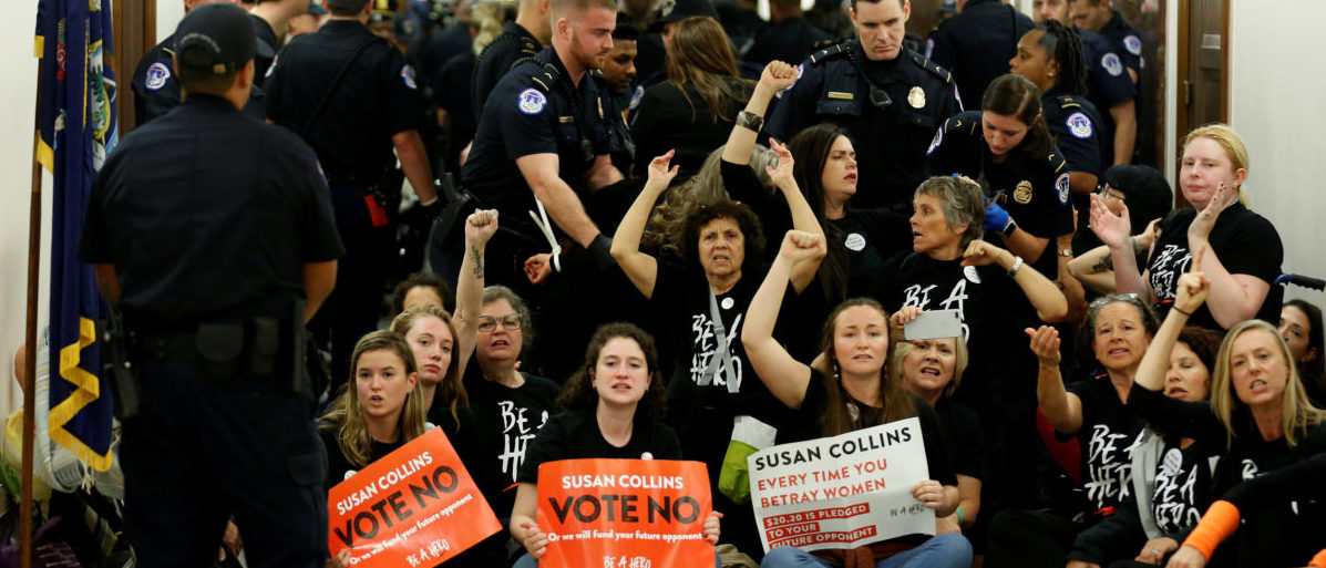 Demonstrators chant before being arrested as they protest against U.S. Supreme Court nominee Brett Kavanaugh in front of the office of Senator Susan Collins (R-ME) on Capitol Hill in Washington, U.S., September 24, 2018. REUTERS/Joshua Roberts TPX IMAGES OF THE DAY