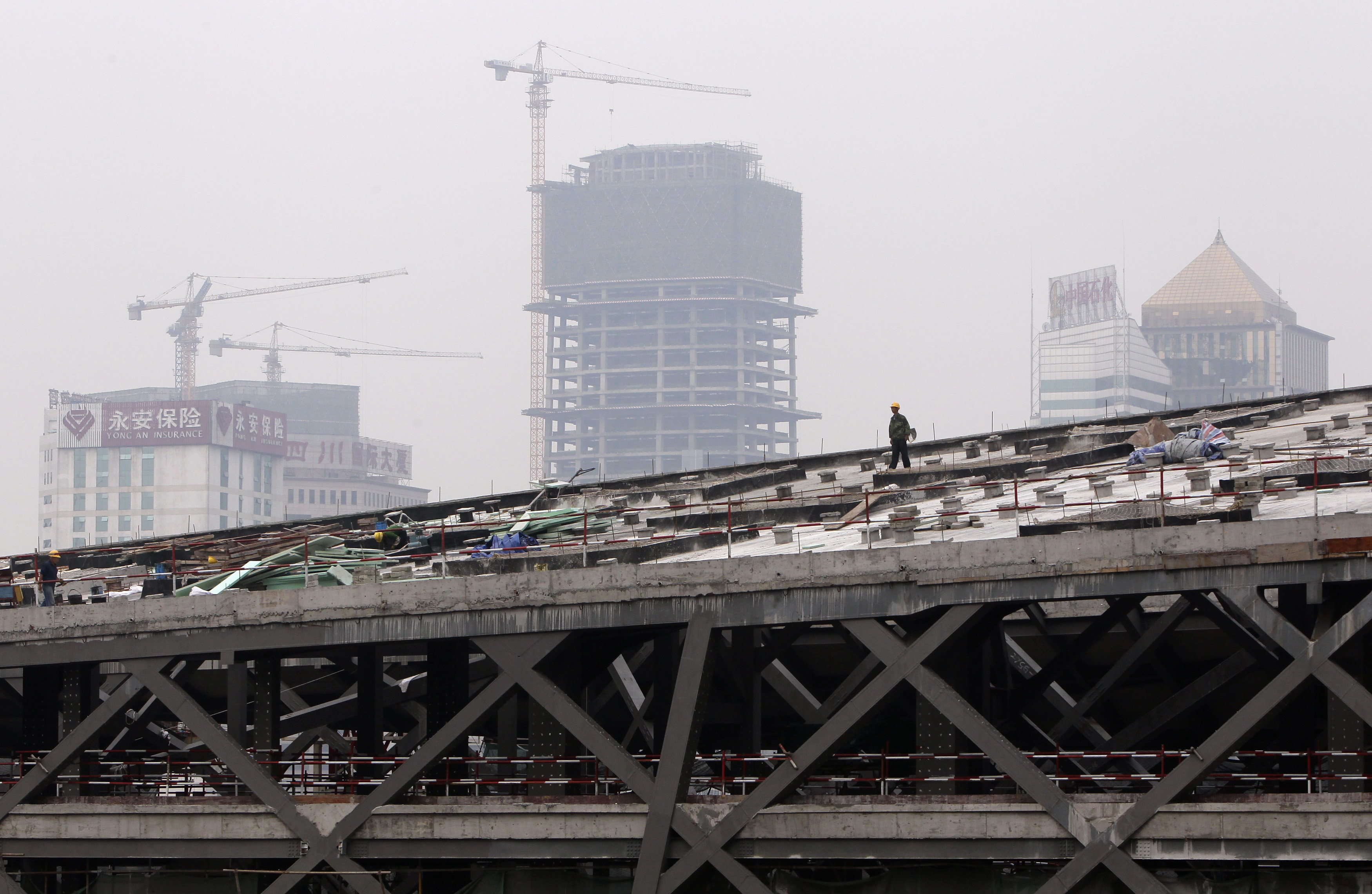 A labourer walks on the top of a construction site in Chengdu September 18, 2012. China's top leaders have pledged to step up policy fine-tuning in the second half of 2012 to bolster an economy that slowed to its weakest pace of growth in more than three years in the second quarter. REUTERS/Jason Lee
