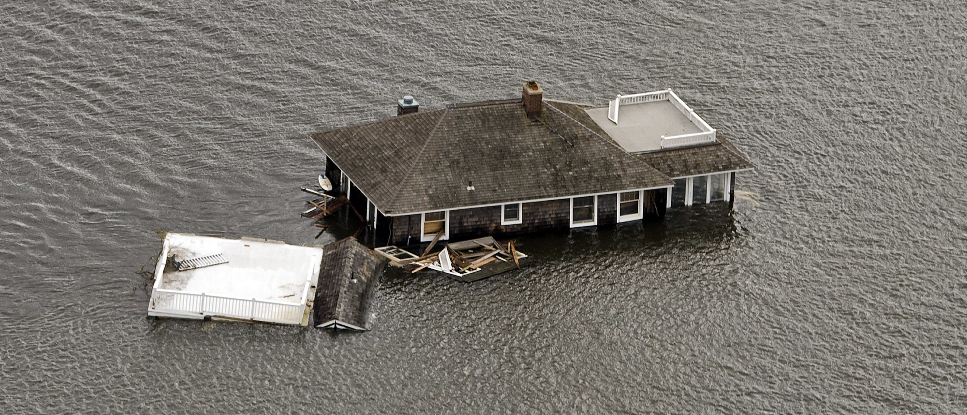 A house floats in the bay after it was washed from its foundation during Hurricane Sandy in Manotoloking, New Jersey October 31, 2012. The U.S. Northeast began an arduous slog back to normal on Wednesday after historic monster storm Sandy crippled transportation, knocked out power for millions and killed at least 64 people with a massive storm surge that caused epic flooding. REUTERS/Steve Nesius (UNITED STATES - Tags: ENVIRONMENT DISASTER) - GM1E8B10BZH01