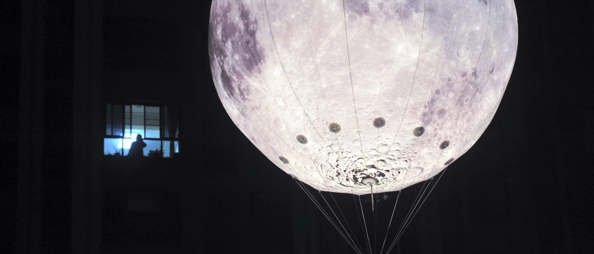 A balloon in the shape of the moon is seen floating next to a residential building to celebrate the Mid-Autumn Festival, in Chengdu, Sichuan province, China, September 26, 2015. The Mid-Autumn Festival is celebrated on the 15th day of the eighth month in the lunar calendar during a full moon, which falls on September 27. Picture taken September 26, 2015. REUTERS/Western China Metropolis Daily's/Lv Jia