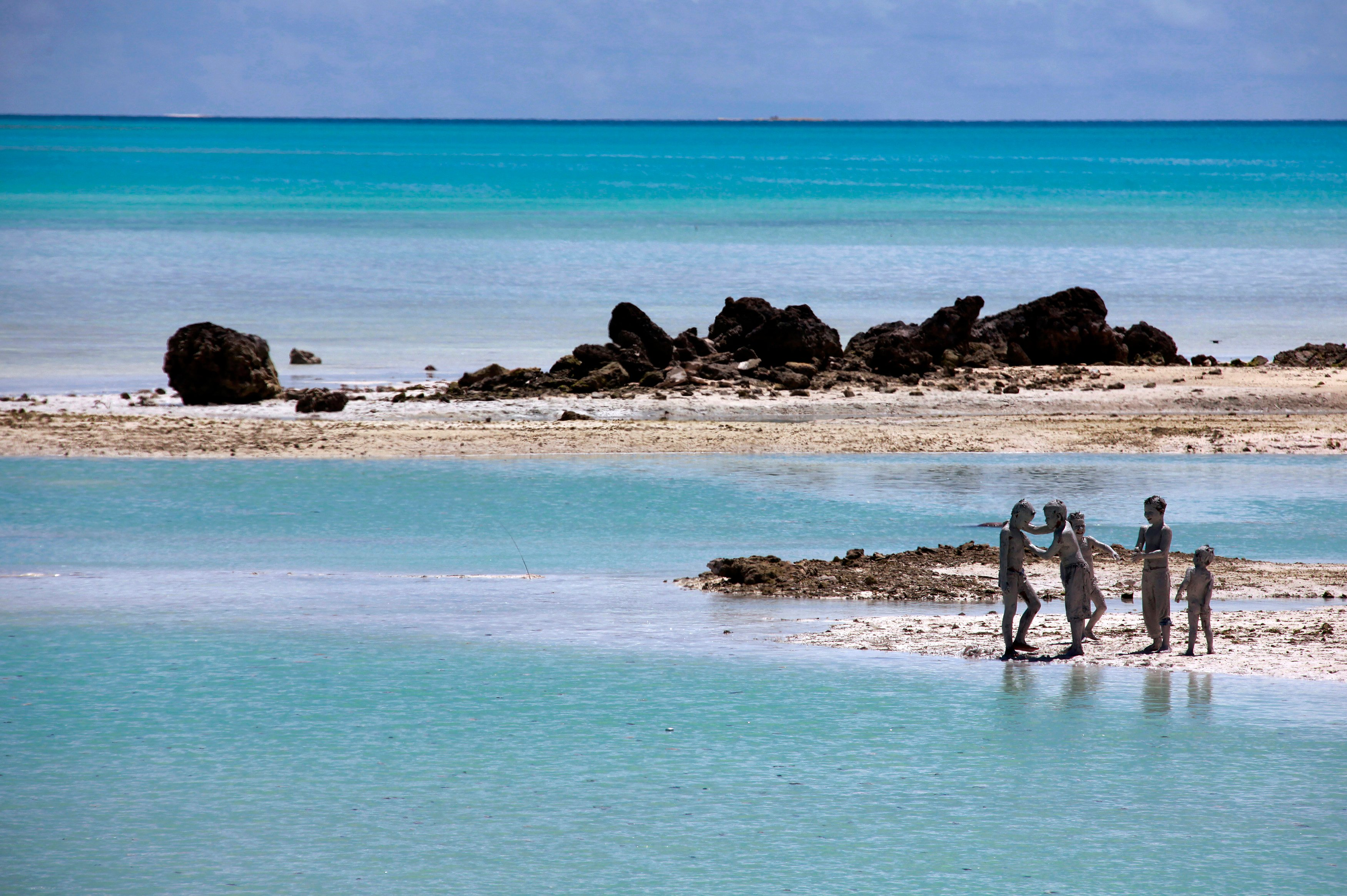 Young boys cover each other in reef-mud near the village of Ambo on South Tarawa in the central Pacific island nation of Kiribati