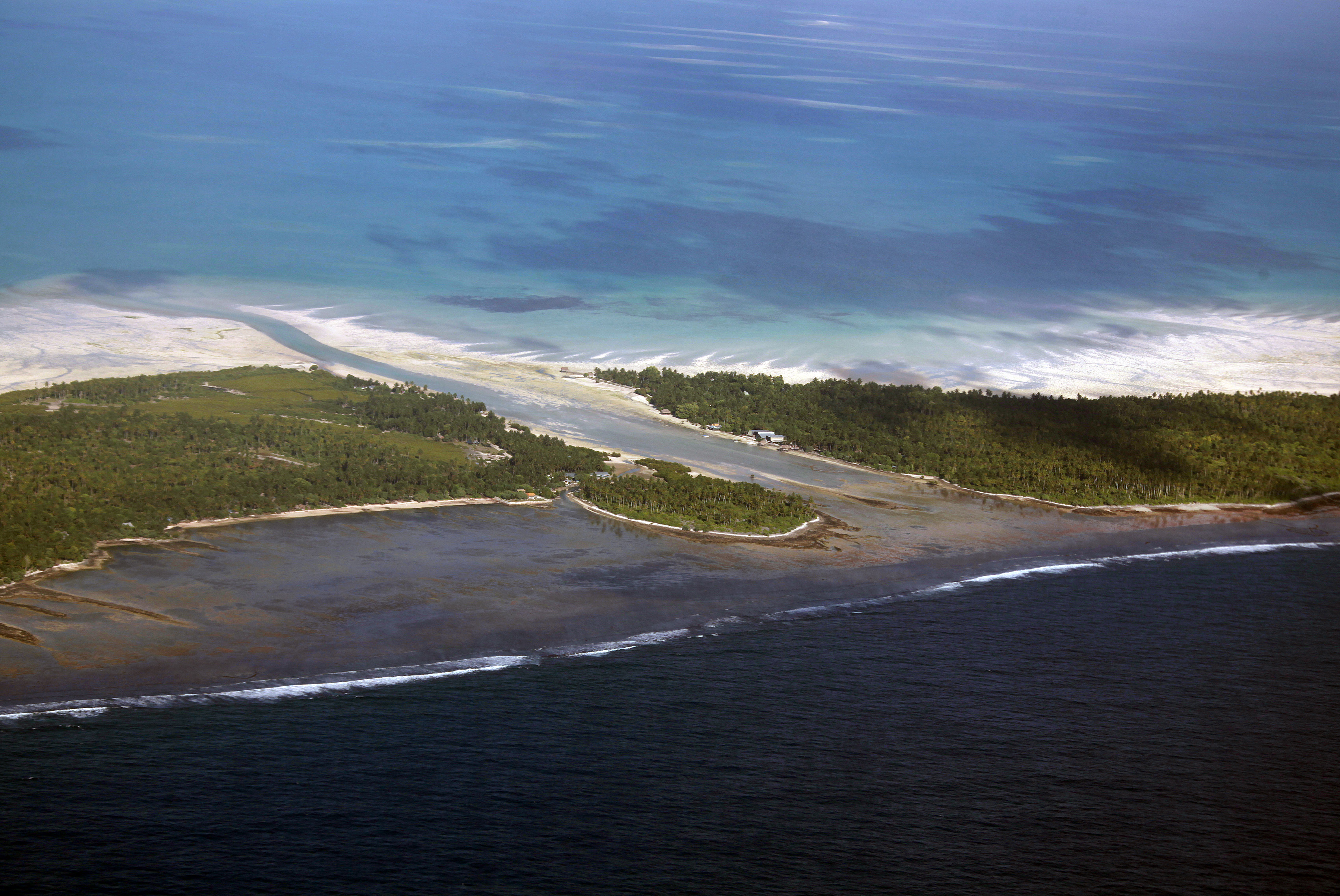 A channel runs between small areas of land on North Tarawa located in the central Pacific island nation of Kiribati