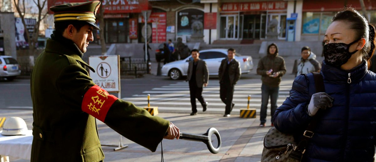 A pedestrian reacts as a security officer holds out a detector on a street in Urumqi, Xinjiang Uighur autonomous region, November 17, 2013. Eleven people were killed and two were injured in China's far-west region of Xinjiang when a group of people armed with axes and knifes attacked a police station on Saturday, state media reported. Picture taken November 17, 2013. REUTERS/Rooney Chen