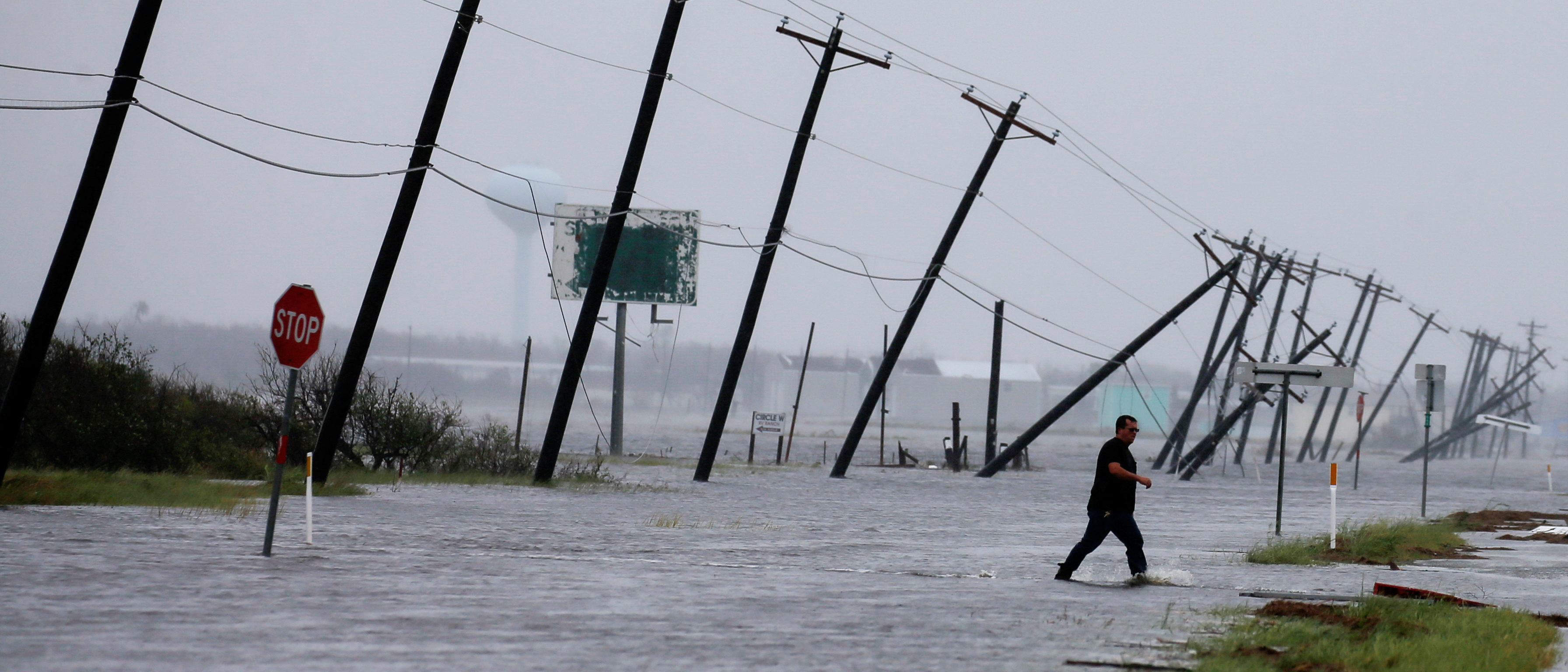 A man walks through floods waters and onto the main road after surveying his property which was hit by Hurricane Harvey in Rockport, Texas, U.S. August 26, 2017. REUTERS/Adrees Latif - RC11AE0B7710