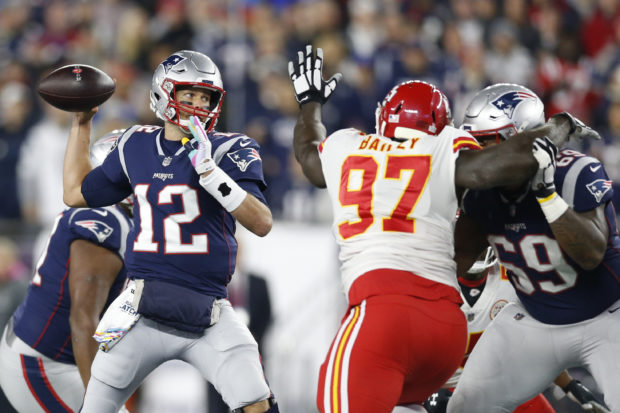 Oct 14, 2018; Foxborough, MA, USA; New England Patriots quarterback Tom Brady (12) makes a pass while pressured by Kansas City Chiefs defensive end Allen Bailey (97) during the first quarter at Gillette Stadium. Mandatory Credit: Greg M. Cooper-USA TODAY Sports - 11445237