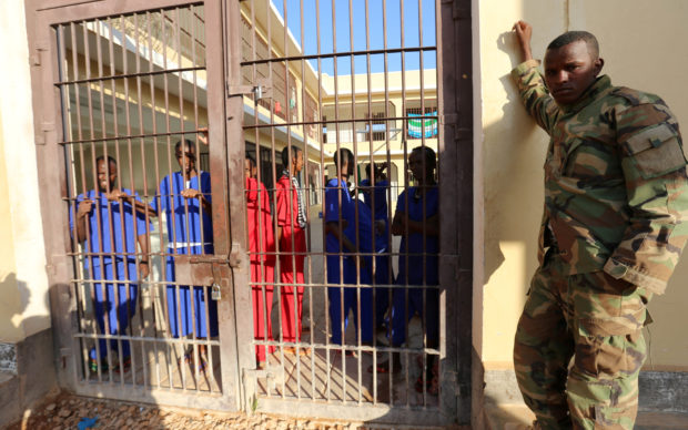 FILE PHOTO: Former Somali pirates stand behind bars in a yard at the Garowe prison where they are serving sentences in the Puntland region of northeastern Somalia, December 14, 2016. REUTERS/Feisal Omar/File Photo - RC1A411BA420