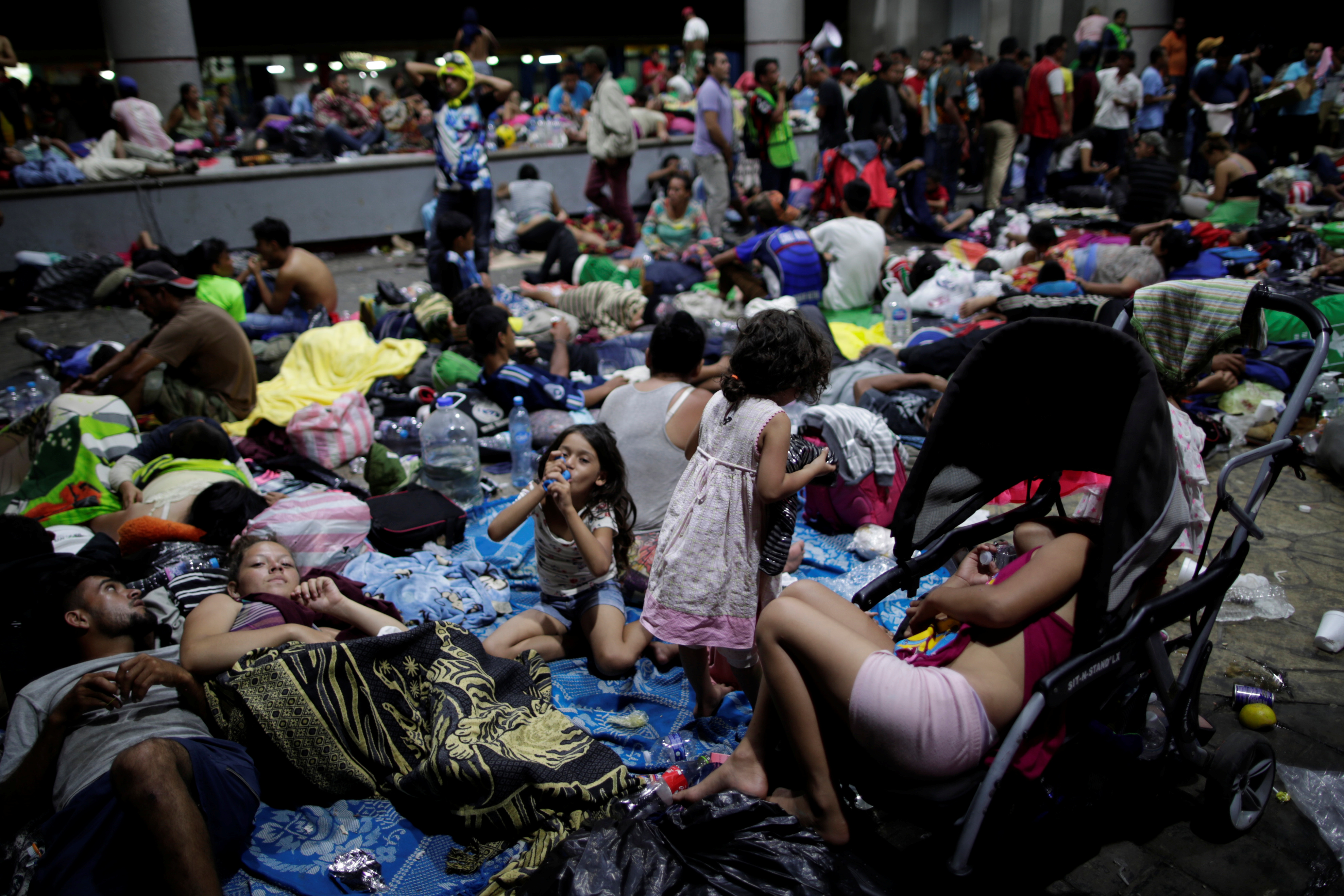 Migrants, part of a caravan of thousands of migrants from Central America en route to the United States, rest along the sidewalks of Tapachula city center, Mexico October 21, 2018.