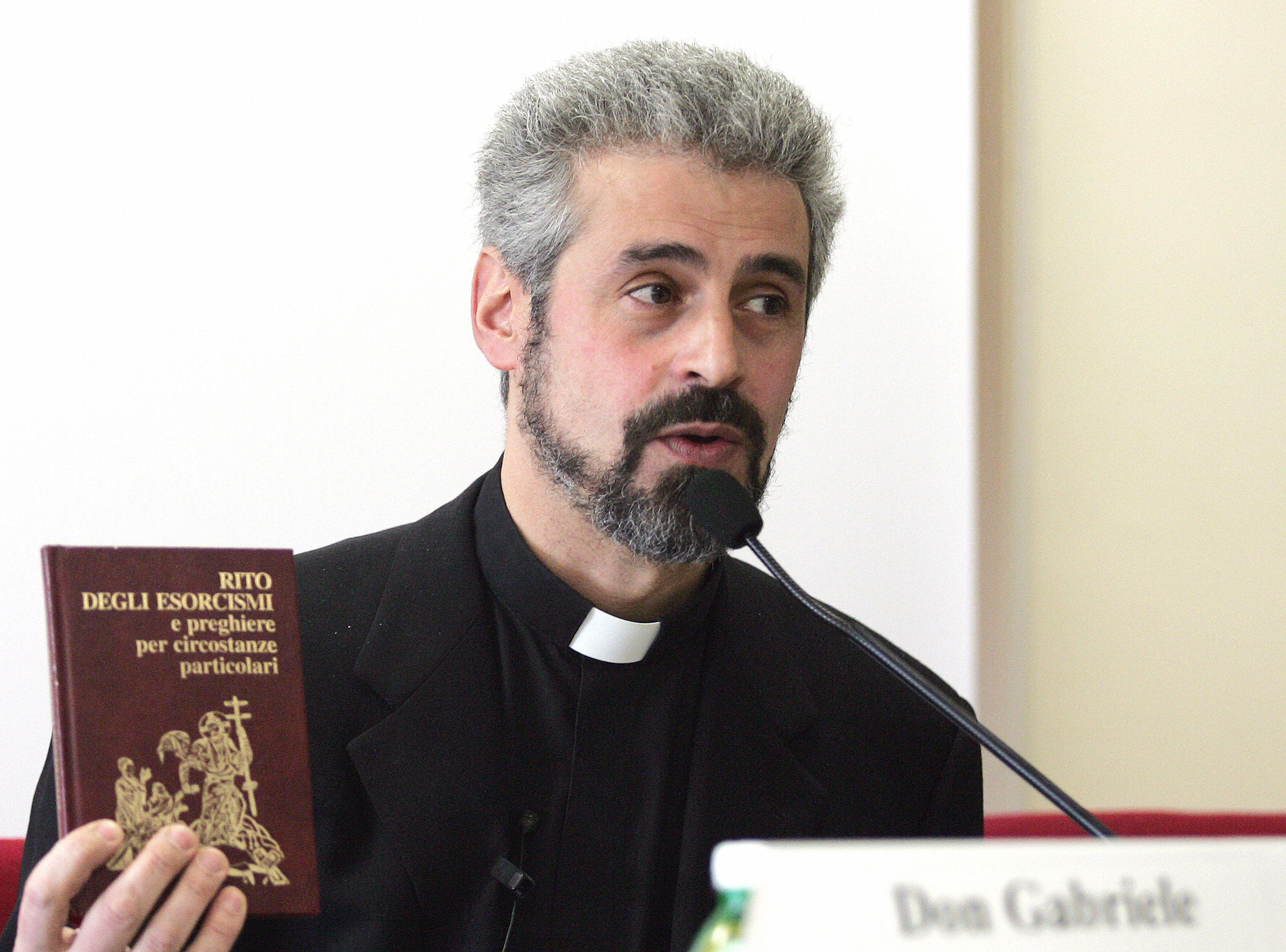 "ROME, ITALY: Father Gabriele Nanni, an official exorcist of the Roman Catholic church, holds the Catholic Church's official book of excorcism ""Rito Degli Esorcismi e preghiere per circostanze particolari"" (Rituals of exorcisms and prayers for specific circumstances) during his lesson at the Regina Apostolorum pontifical university in Rome 17 February 2005. Around one hundred priests today attended the first lesson on satanism and exorcism at the Vatican-linked Regina Apostolorum university. (ALBERTO PIZZOLI/AFP/Getty Images)"
