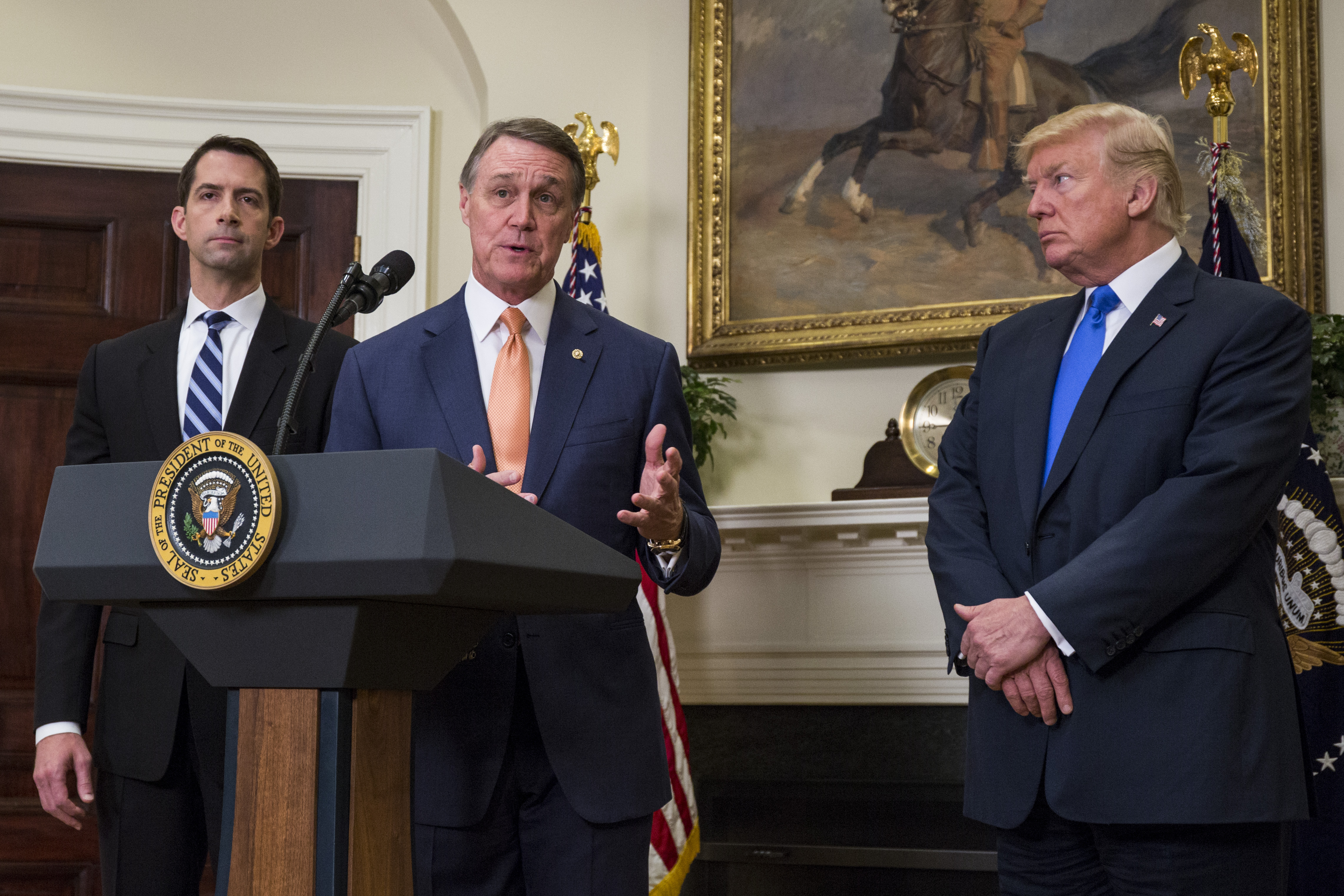 "WASHINGTON, DC - AUGUST 2: (AFP OUT) Sen. David Perdue (R-GA) makes an announcement on the introduction of the Reforming American Immigration for a Strong Economy (RAISE) Act in the Roosevelt Room at the White House on August 2, 2017 in Washington, DC. The act aims to overhaul U.S. immigration by moving towards a ""merit-based"" system. Also pictured are Sen. Tom Cotton (R-AR) left, and U.S. President Donald Trump, right.(Photo by Zach Gibson - Pool/Getty Images)"