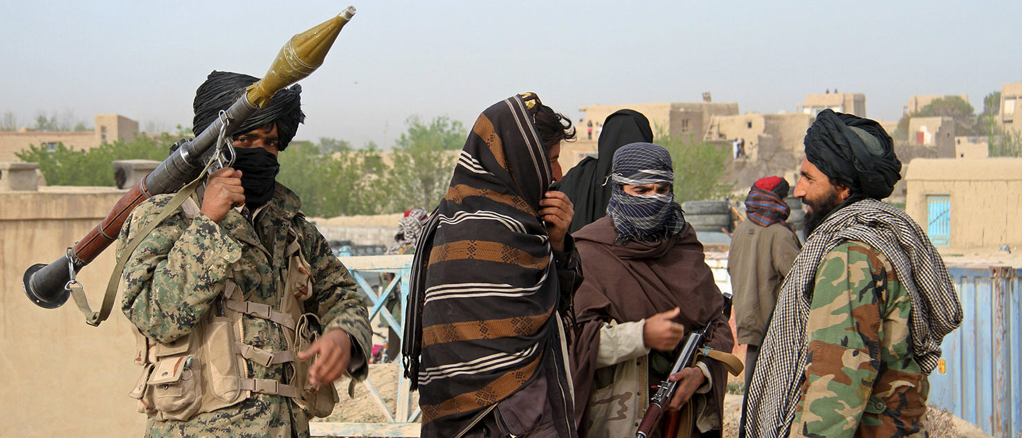 Members of the Taliban gather at the site of the execution of three men accused of murdering a couple during a robbery in Ghazni Province April 18, 2015. The Taliban announced the execution of the three men accused of murdering a couple during a robbery, saying they had been tried by an Islamic court. The killing was carried out in front of a crowd by Taliban fighters who fired at the men with AK-47s, according to a Reuters witness. Footage seen by Reuters show the men were made to sit on the ground with their eyes blindfolded and their hands tied at the time of their execution. REUTERS/Stringer