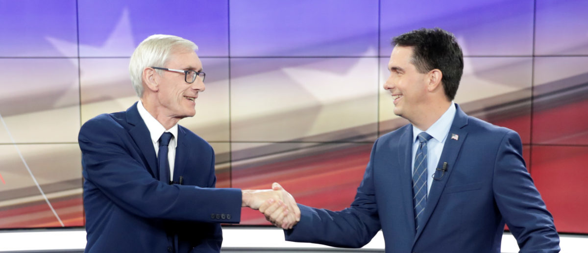 Democratic challenger Tony Evers (L) and Wisconsin Gov. Scott Walker (R) shake hands during a media availability before the start of the gubernatorial debate hosted by the Wisconsin Broadcasters Association Foundation in Madison, Wisconsin, U.S., October 19, 2018. Picture taken on October 19, 2018. Steve Apps/Wisconsin State Journal