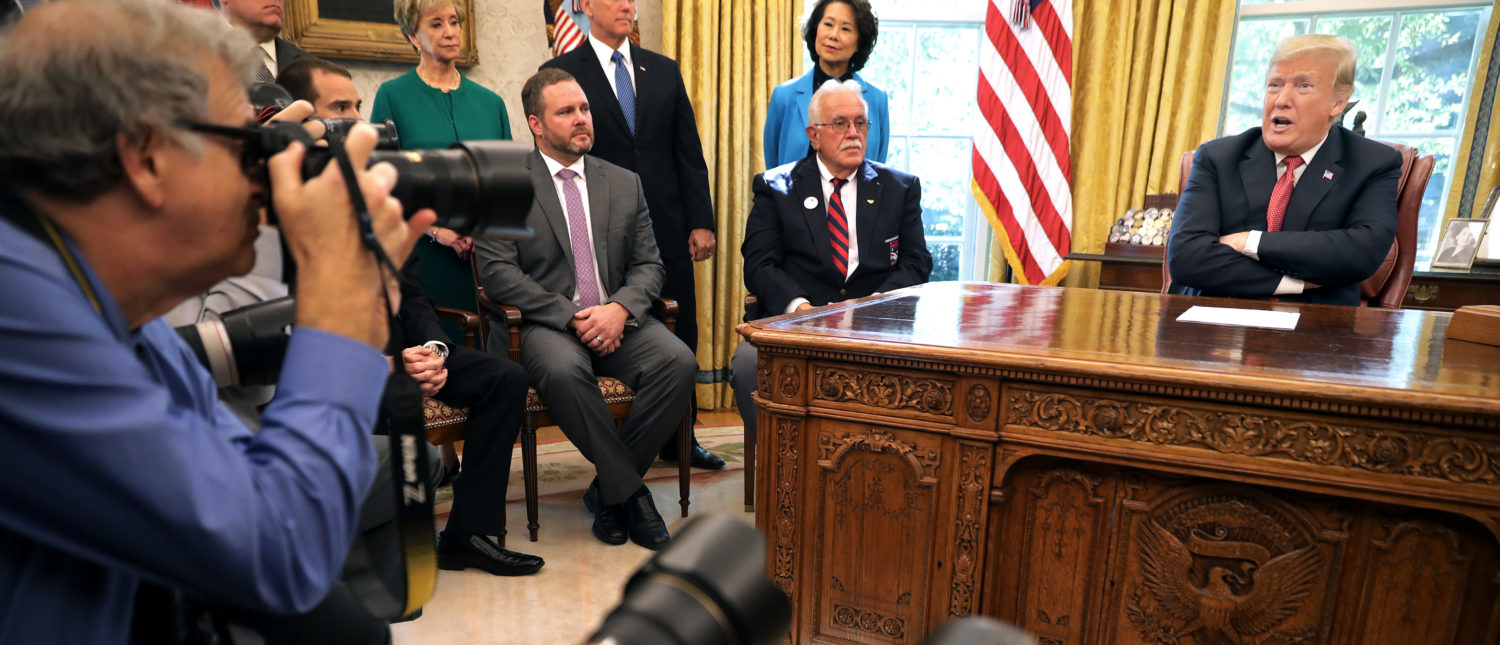 """WASHINGTON, DC - OCTOBER 17: U.S. President Donald Trump (R) talks to reporters while hosting workers and members of his cabinet for a meeting in the Oval Office at the White House October 17, 2018 in Washington, DC. The White House said the meeting was on """"Cutting the Red Tape, Unleashing Economic Freedom."""" (Photo by Chip Somodevilla/Getty Images)"""
