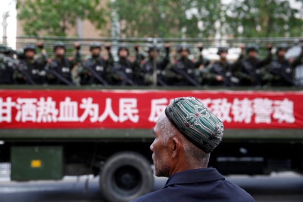 "FILE PHOTO: A Uighur man looks on as a truck carrying paramilitary policemen travel along a street during an anti-terrorism oath-taking rally in Urumqi, Xinjiang Uighur Autonomous Region, China May 23, 2014. The Chinese characters on the banner read, ""Willingness to spill blood for the people. Countering terrorism and fighting the enemies is part of the police spirit."" REUTERS/Stringer/File Photo"