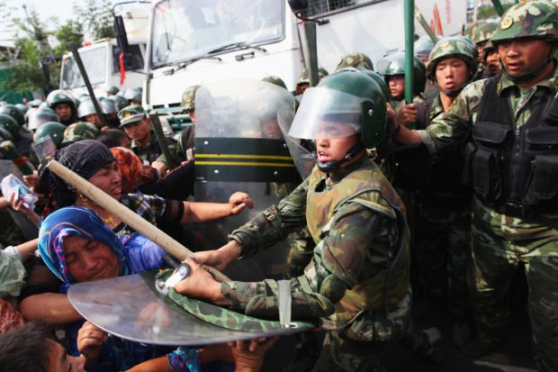 URUMQI, CHINA - JULY 07: Chinese policemen push Uighur women who are protesting at a street on July 7, 2009 in Urumqi, the capital of Xinjiang Uighur autonomous region, China. Hundreds of Uighur people have taken to the streets protesting after their relatives were detained by authorities after Sunday's protest. Ethnic riots in the capital of the Muslim Xinjiang region on Sunday saw 156 people killed. Police officers, soldiers and firefighters were dispatched to contain the rioting with hundreds of people being detained. (Photo by Guang Niu/Getty Images)