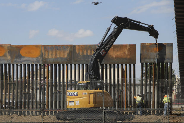 """Workers in El Paso Texas, in the US, replace a section of the Mexico-US border fence next to the international border bridge """"Paso del Norte"""" as seen from Ciudad Juarez, in Chihuahua state, Mexico, on September 26, 2018. HERIKA MARTINEZ/AFP/Getty Images"""