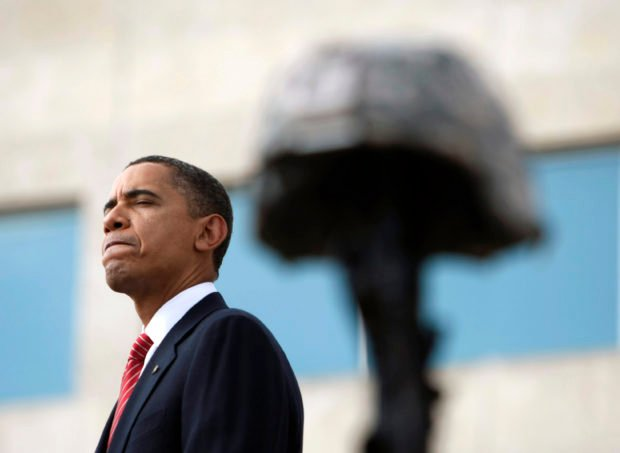 President Barack Obama pauses as he speaks behind the helmet and weapon of one of the fallen soldiers during the III Corps and Fort Hood Memorial Ceremony November 10, 2009 held to honor the victims of the shootings on the Fort Hood Army post in Fort Hood, Texas. REUTERS/Kevin Lamarque