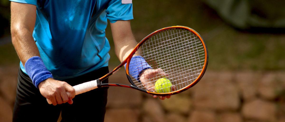 A tennis player prepares to serve a tennis ball during a match (SHUTTERSTOCK By Maxisport)