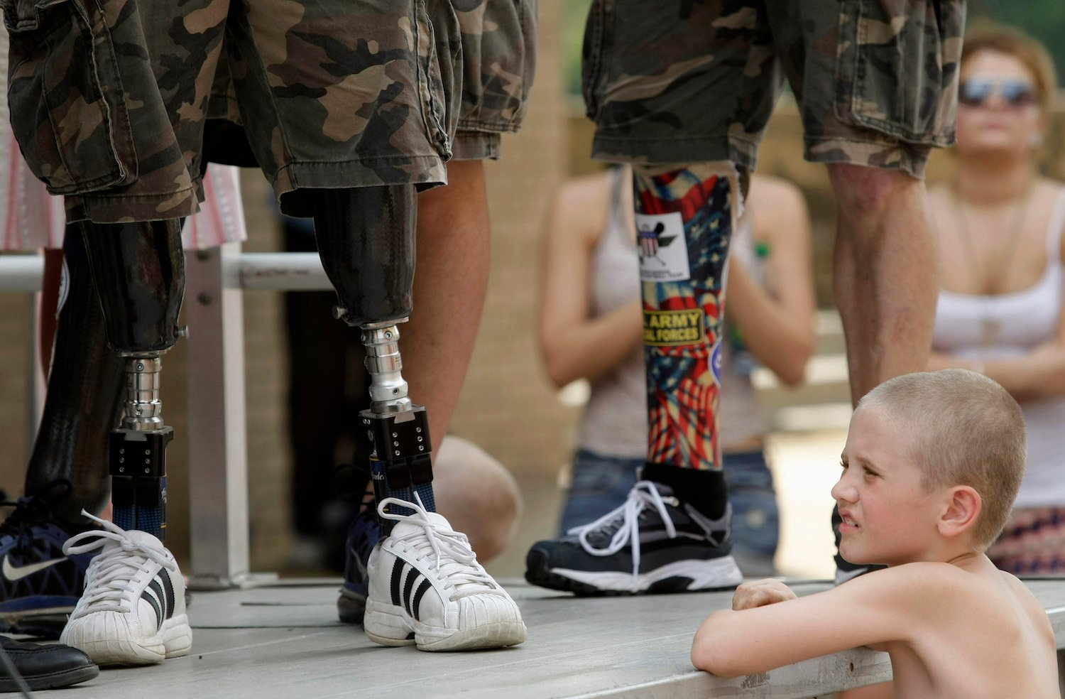 A child looks at the prosthetic legs of Wounded Warrior Amputee. REUTERS/Gary Cameron/Files