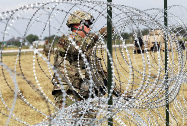 A U.S. Army soldier from Ft. Riley, Kansas, installs barbed wire fence for an encampment to be used by the military near the U.S. Mexico border in Donna, Texas, U.S., Nov. 4, 2018. REUTERS/Del is Lopez