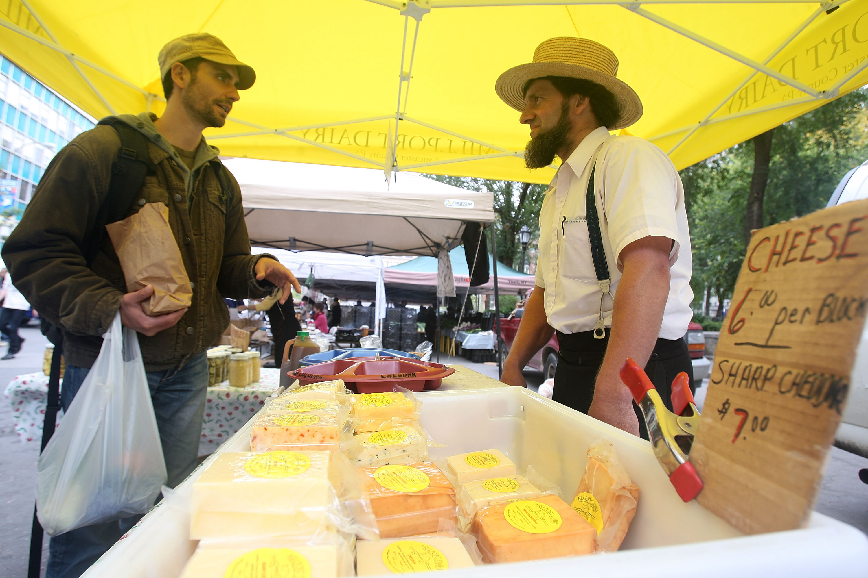 NEW YORK - OCTOBER 02: Amish farmer John Stoltzfoos (R) talks with a customer at the Union Square farmers market October 2, 2009 in New York City. (Photo by Mario Tama/Getty Images)