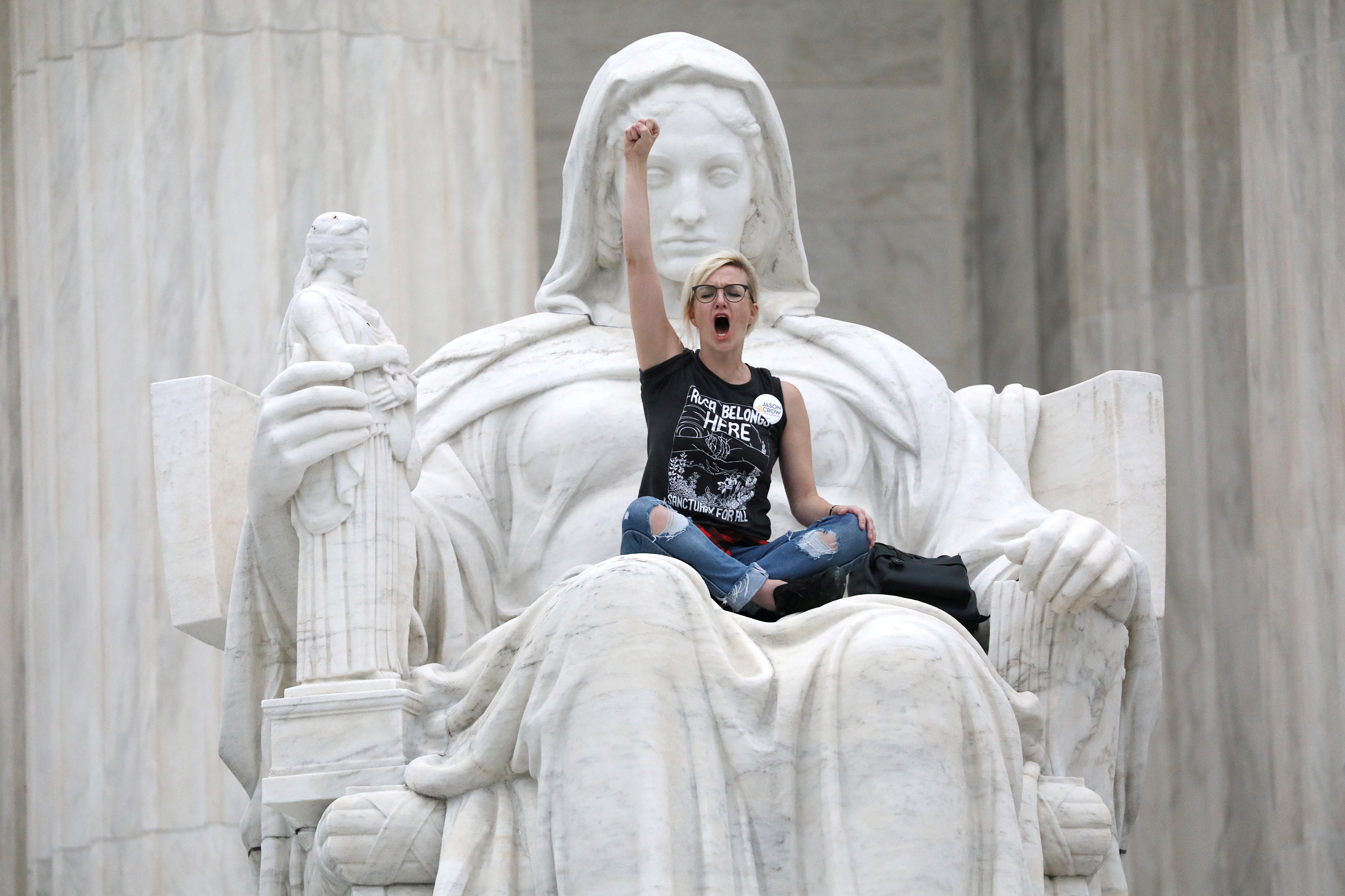 "A protester sits on the lap of ""Lady Justice"" on the steps of the U.S. Supreme Court building as demonstrators storm the steps and doors while Judge Brett Kavanaugh is inside being sworn in as an justice. REUTERS/Jonathan Ernst"
