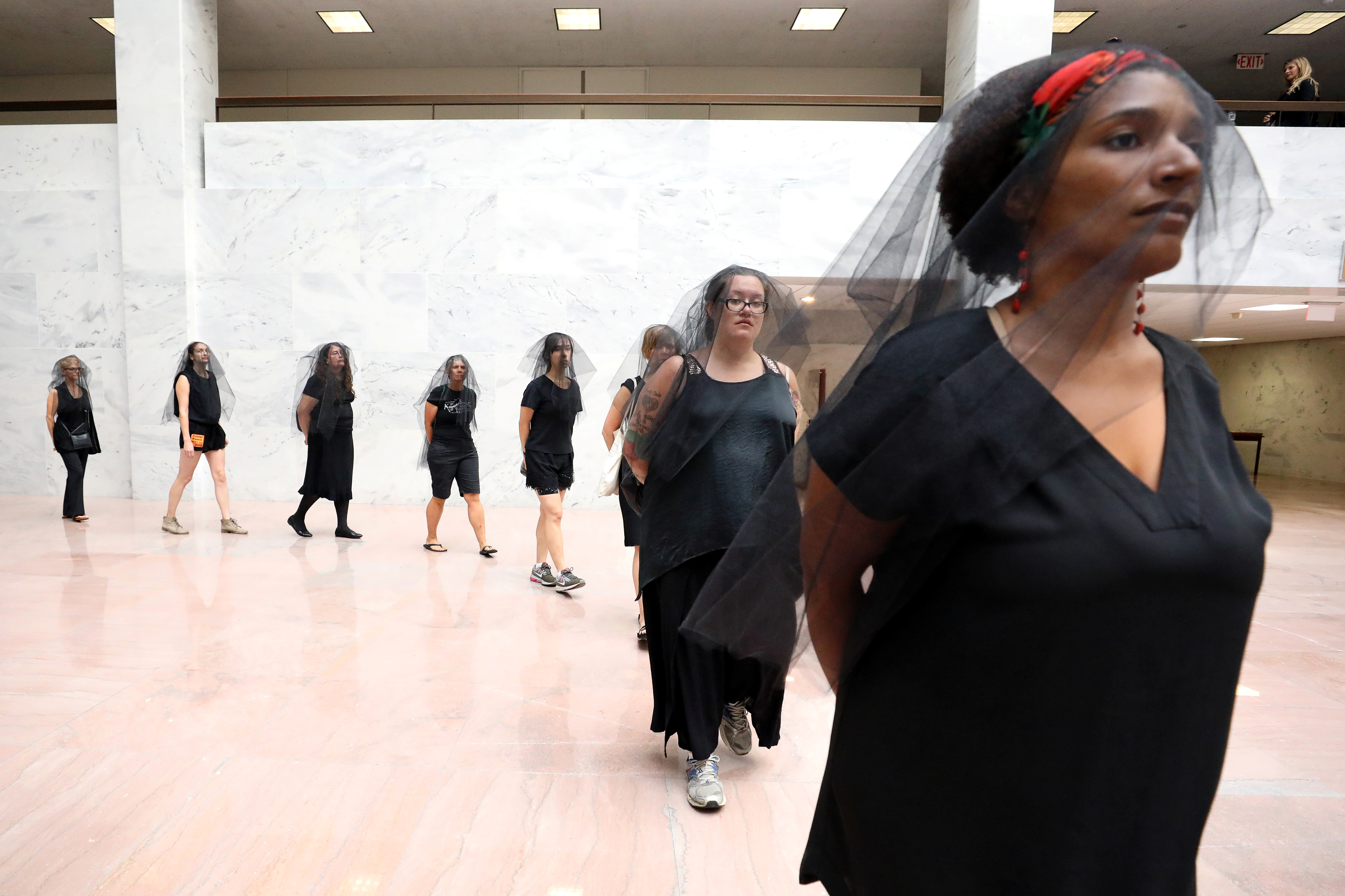 Protesters wearing black veils leave the Hart Senate Office Building on the fourth day of Senate Judiciary Committee confirmation hearings for U.S. Supreme Court nominee Judge Brett Kavanaugh on Capitol Hill in Washington, U.S., September 7, 2018. REUTERS/Chris Wattie