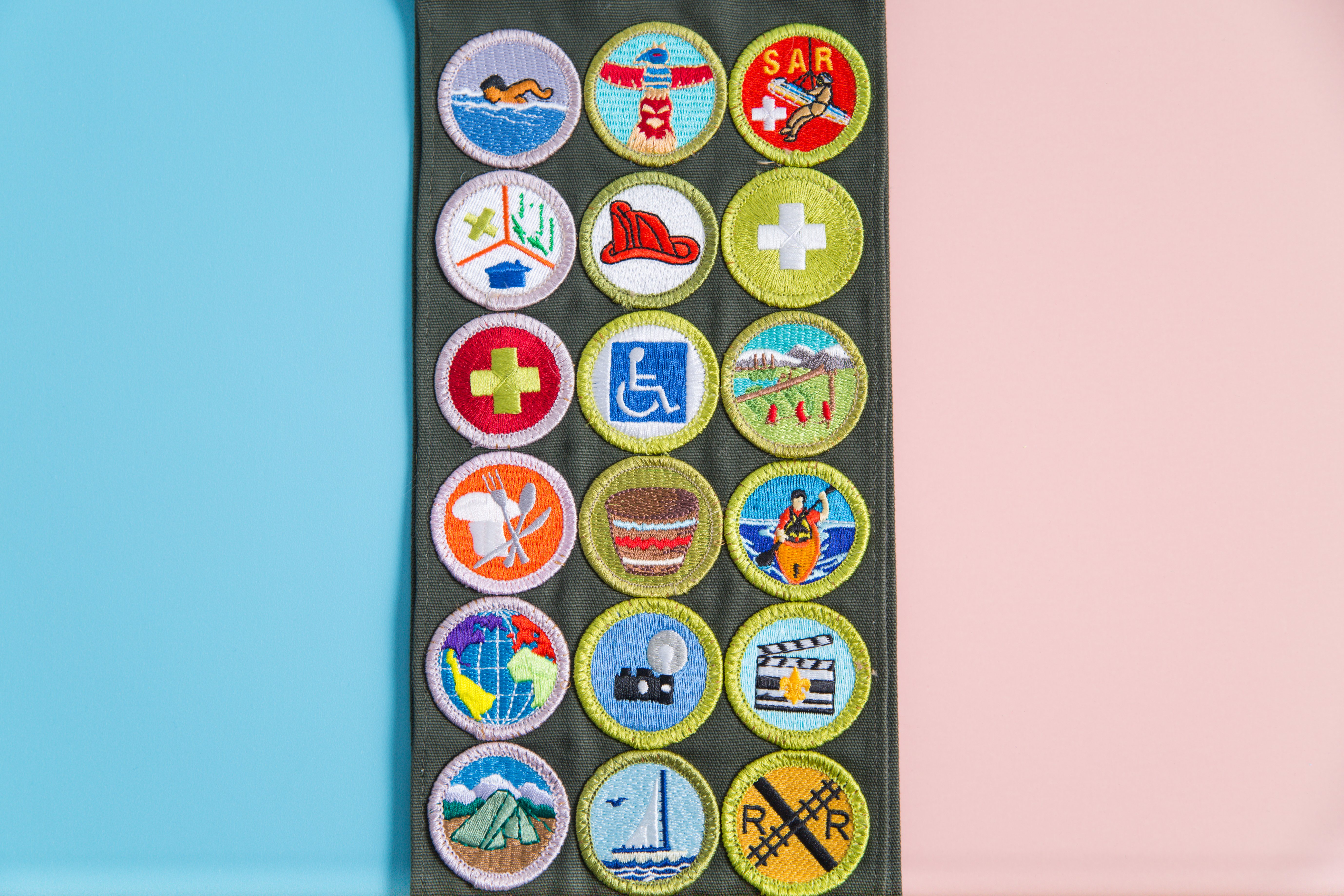 Boy Scouts of America (BSA) merit badge sash on pink and blue background as BSA welcomes girls to join scouting. SHUTTERSTOCK/ Amy Kerkemeyer