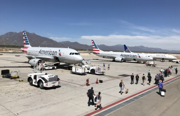 Passengers walk on the tarmac to board an American Airlines plane at Los Cabos International Airport, in Los Cabos, Baja California Sur state, Mexico on March 14, 2018. Despite a surge of violent crimes in popular tourist areas such as Los Cabos and Cancun, tourism is Mexico's third largest source of foreign exchange. In 2017 the country hit a new record -- 39.3 million tourists who generated $21 billion in business. (DANIEL SLIM/AFP/Getty Images)