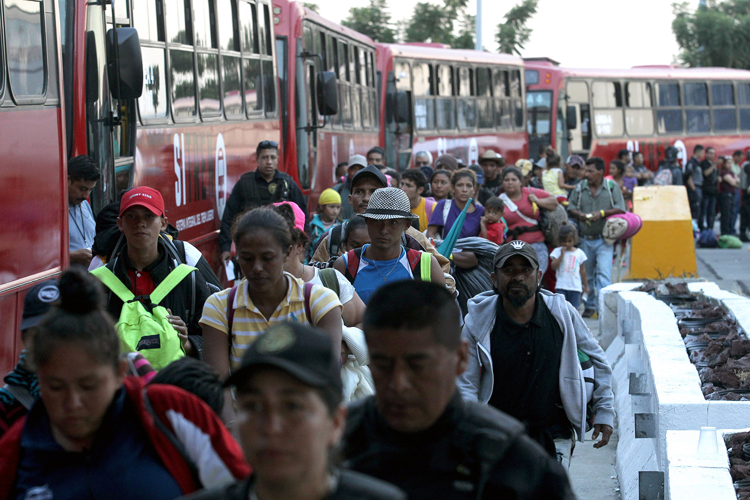 Central American migrants -mostly Hondurans- moving in a caravan towards the United States, board buses to head to a shelter in the outskirts of Zapotlanejo, Jalisco state, Mexico, on November 11, 2018. - The United States embarked Friday on a policy of automatically rejecting asylum claims of people who cross the Mexican border illegally in a bid to deter Central American migrants and force Mexico to handle them. ULISES RUIZ/AFP/Getty Images