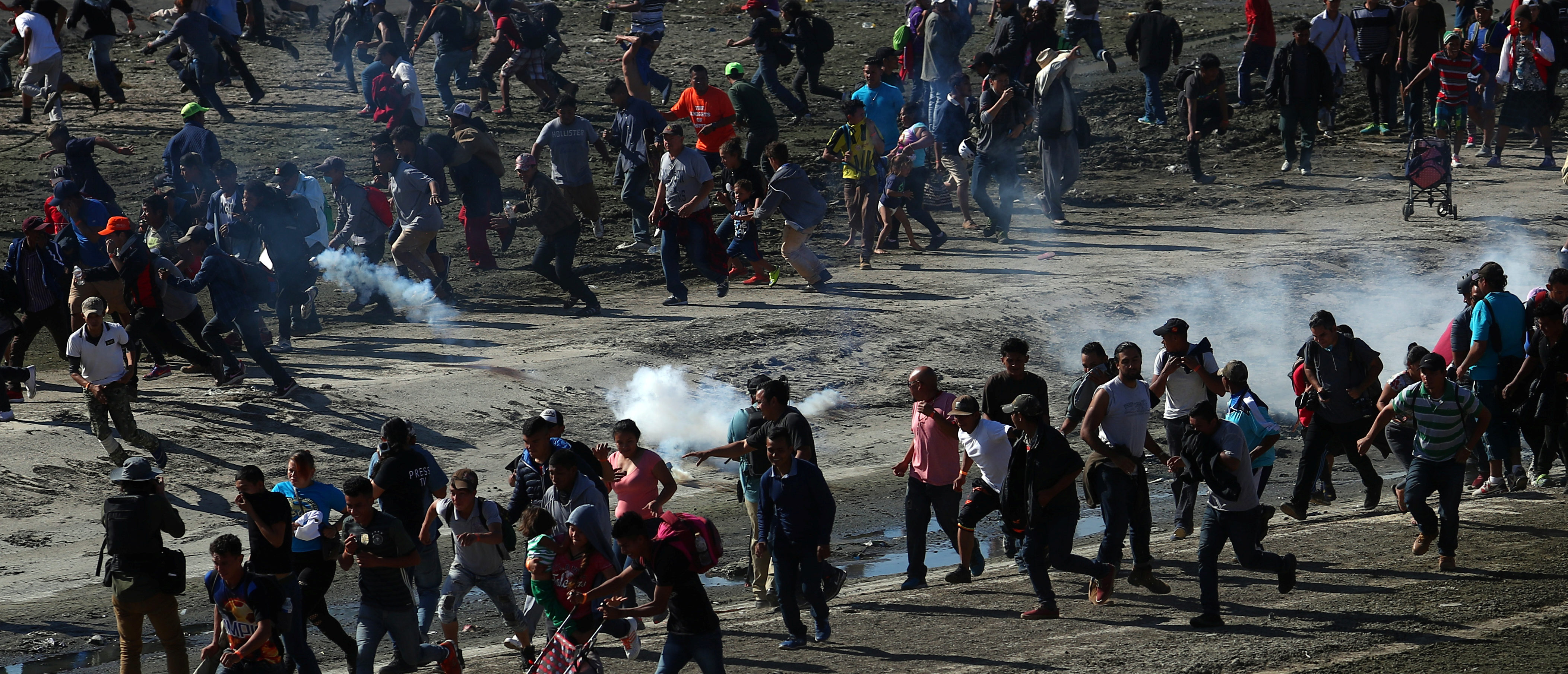 Migrants, part of a caravan of thousands from Central America trying to reach the United States, run from tear gas released by U.S border patrol, near the border fence between Mexico and the United States in Tijuana, Mexico, November 25, 2018. REUTERS/Hannah McKay