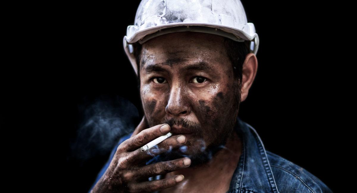 Close up worker man smoking. Shutterstock