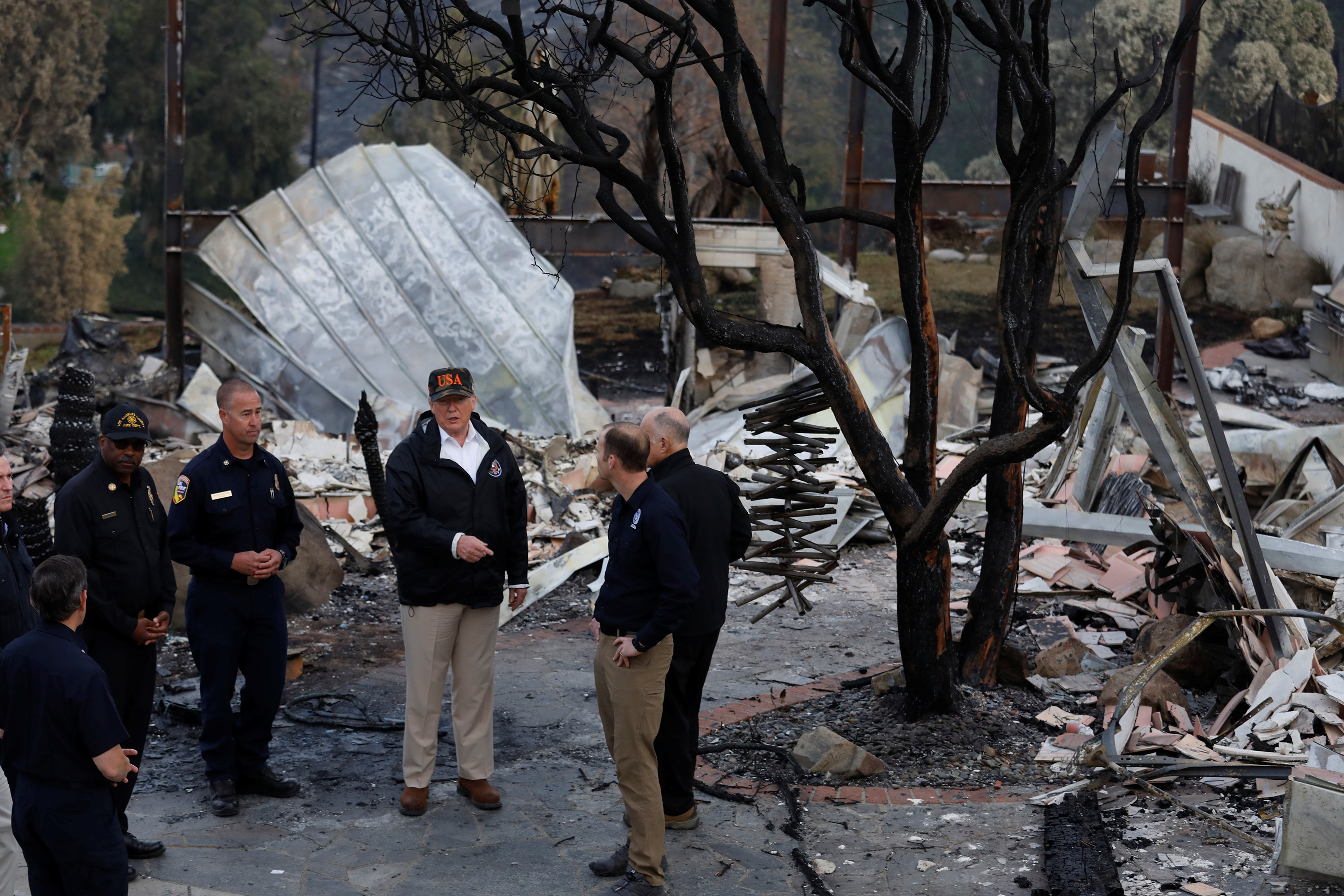 U.S. President Donald Trump (C) surveys homes destroyed by the Woolsey fire with first responders in Malibu, California, U.S., November 17, 2018. Picture taken on November 17, 2018. Genaro Molina/Los Angeles Times/Pool via REUTERS