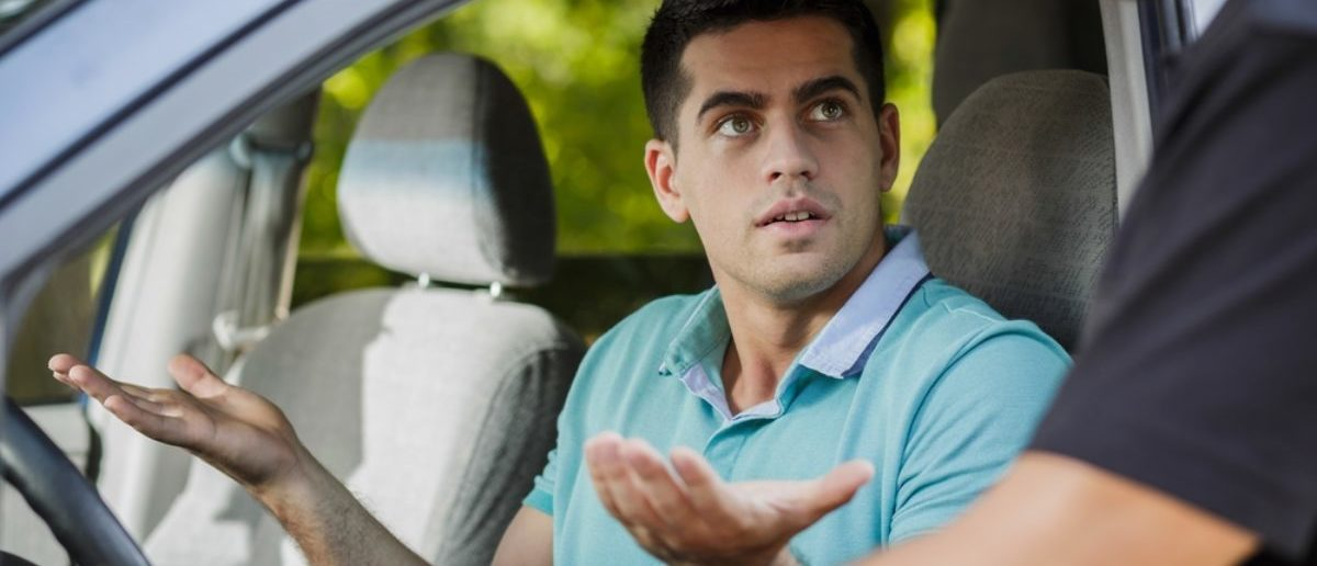 Confused young man in the car stopped by policeman (SHUTTERSTOCK By Photographee.eu)