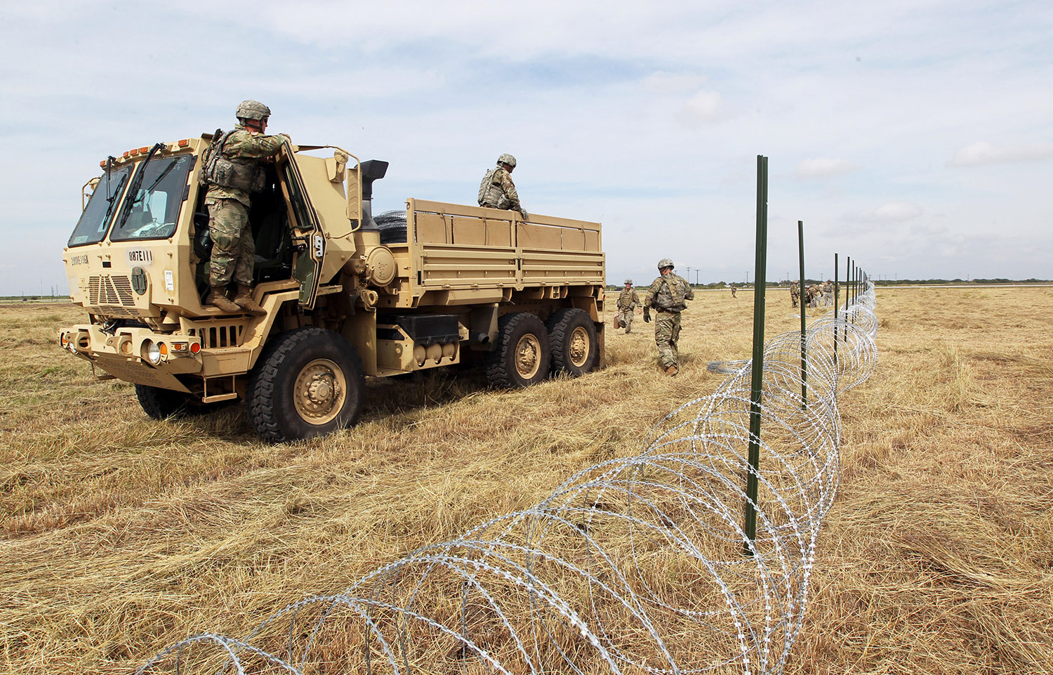 U.S. Army soldiers from Ft. Riley, Kansas, put up razor wire fence for an encampment to be used by the military near the U.S. Mexico border in Donna, Texas, U.S., November 4, 2018. REUTERS/Delcia Lopez