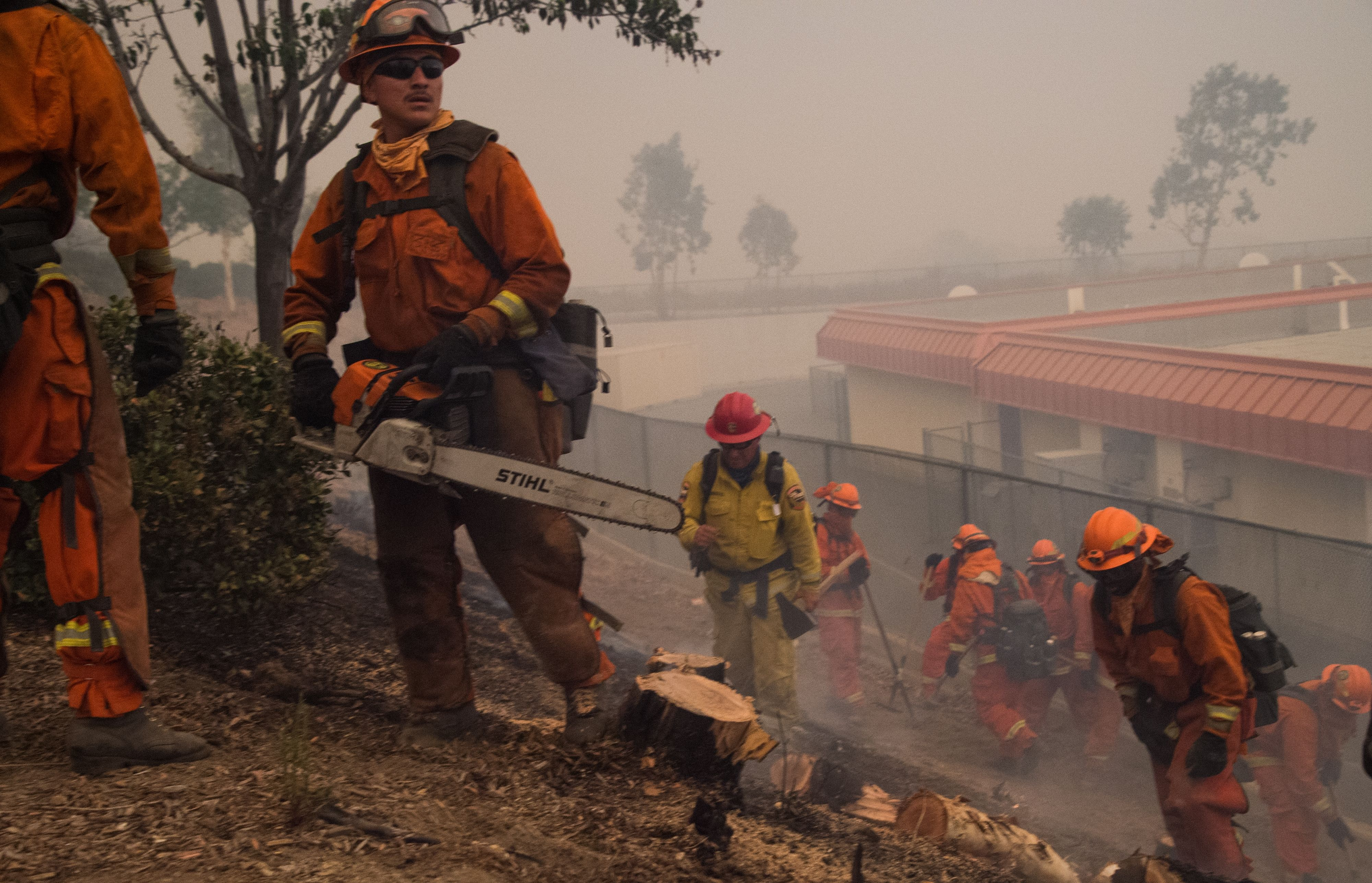 An inmate fire crew clears brush and puts out hotspots to protect an elementary school that almost caught fire at the Holy Fire in Lake Elsinore, California, southeast of Los Angeles, on August 9, 2018. - A man suspected of intentionally starting the Holy Fire on August 6 in the nearby Cleveland National Forest was charged August 9 with multiple felony counts involving arson. (Photo by Robyn Beck / AFP)