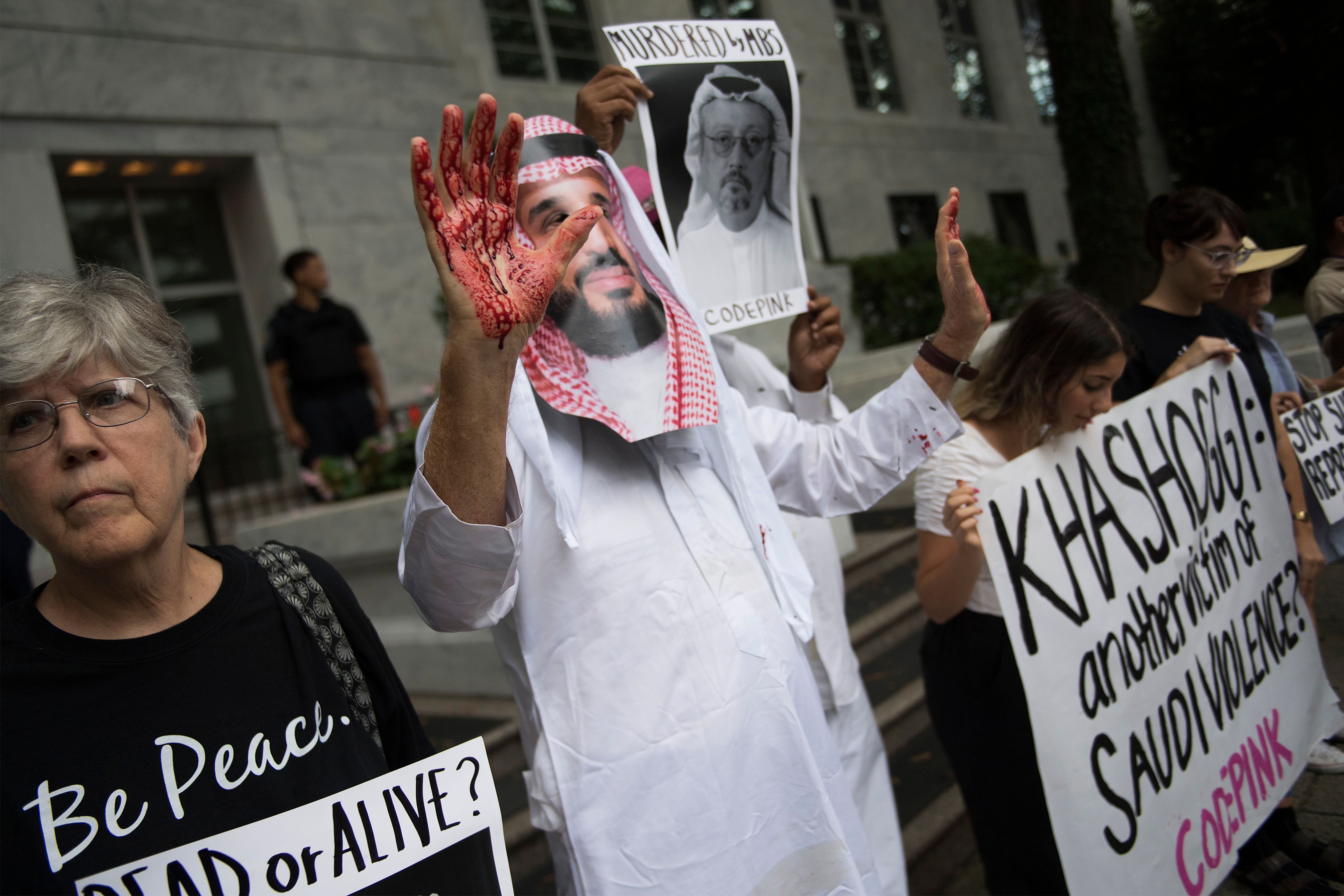 "A demonstrator dressed as Saudi Arabian Crown Prince Mohammed bin Salman (C) with blood on his hands protests outside the Saudi Embassy in Washington, DC, on October 8, 2018, demanding justice for missing Saudi journalist Jamal Khashoggi. - US President Donald Trump said October 10, 2018 he has talked to Saudi authorities ""at the highest level"" to demand answers over what happened to missing journalist Jamal Khashoggi."