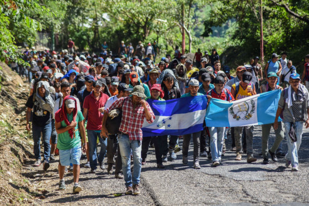 TOPSHOT - Honduran migrants take part in a new caravan heading to the US with Honduran and Guatemalan national flags in Quezaltepeque, Chiquimula, Guatemala on October 22, 2018. - US President Donald Trump on Monday called the migrant caravan heading toward the US-Mexico border a national emergency, saying he has alerted the US border patrol and military. (Photo by ORLANDO ESTRADA / AFP) (Photo credit should read ORLANDO ESTRADA/AFP/Getty Images)