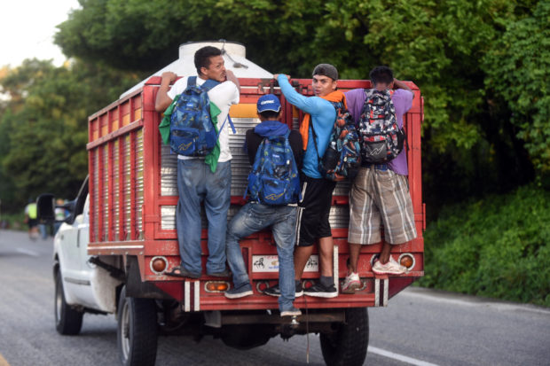 TOPSHOT - Honduran migrants heading in a caravan to the US, travel standing on the back of a truck in Mapastepec on their way to Pijijiapan Chiapas state, Mexico, on October 25, 2018. - Thousands of Central American migrants crossing Mexico toward the United States in a caravan have resumed their long trek, walking about 12 hours to their next destination. (Photo by Johan ORDONEZ / AFP) (Photo credit should read JOHAN ORDONEZ/AFP/Getty Images)