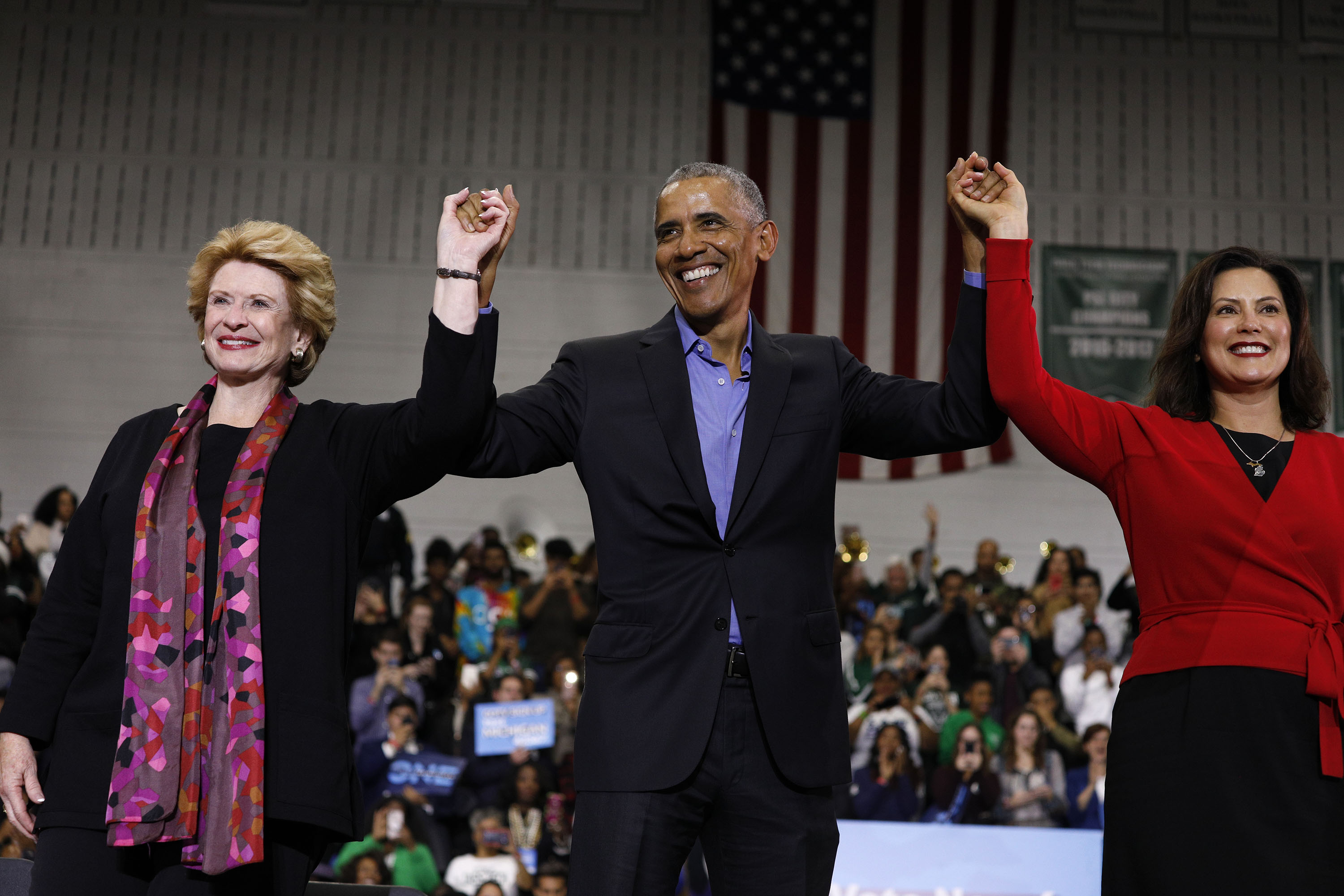 DETROIT, MI - OCTOBER 26: Former President Barack Obama raises his arms with Michigan Senator Debbie Stabenow (L) and Michigan gubernatorial candidate Gretchen Whitmer (R) at a rally to support Michigan democratic candidates at Detroit Cass Tech High School on October 26, 2018 in Detroit, Michigan. Obama, and former Attorney General Eric Holder, who was also at the rally, are among approximately a dozen democrats who were targeted by mail bombs over the past several days. (Photo by Bill Pugliano/Getty Images)