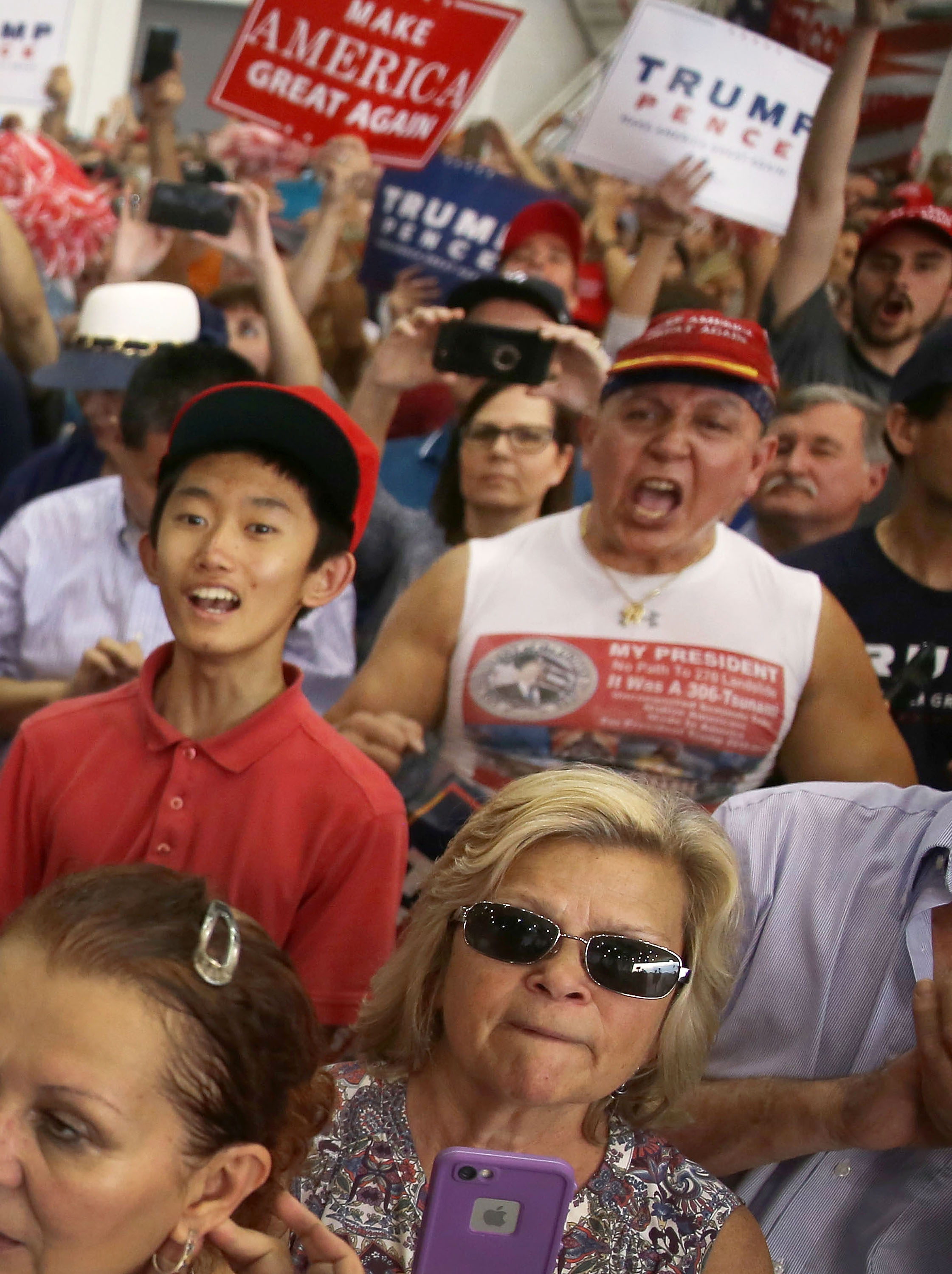 In this file picture from 2017, Cesar Sayoc (far right in red hat) is seen as President Donald Trump speaks during a campaign rally at the AeroMod International hangar at Orlando Melbourne International Airport on February 18, 2017 in Melbourne, Florida. Joe Raedle/Getty Images