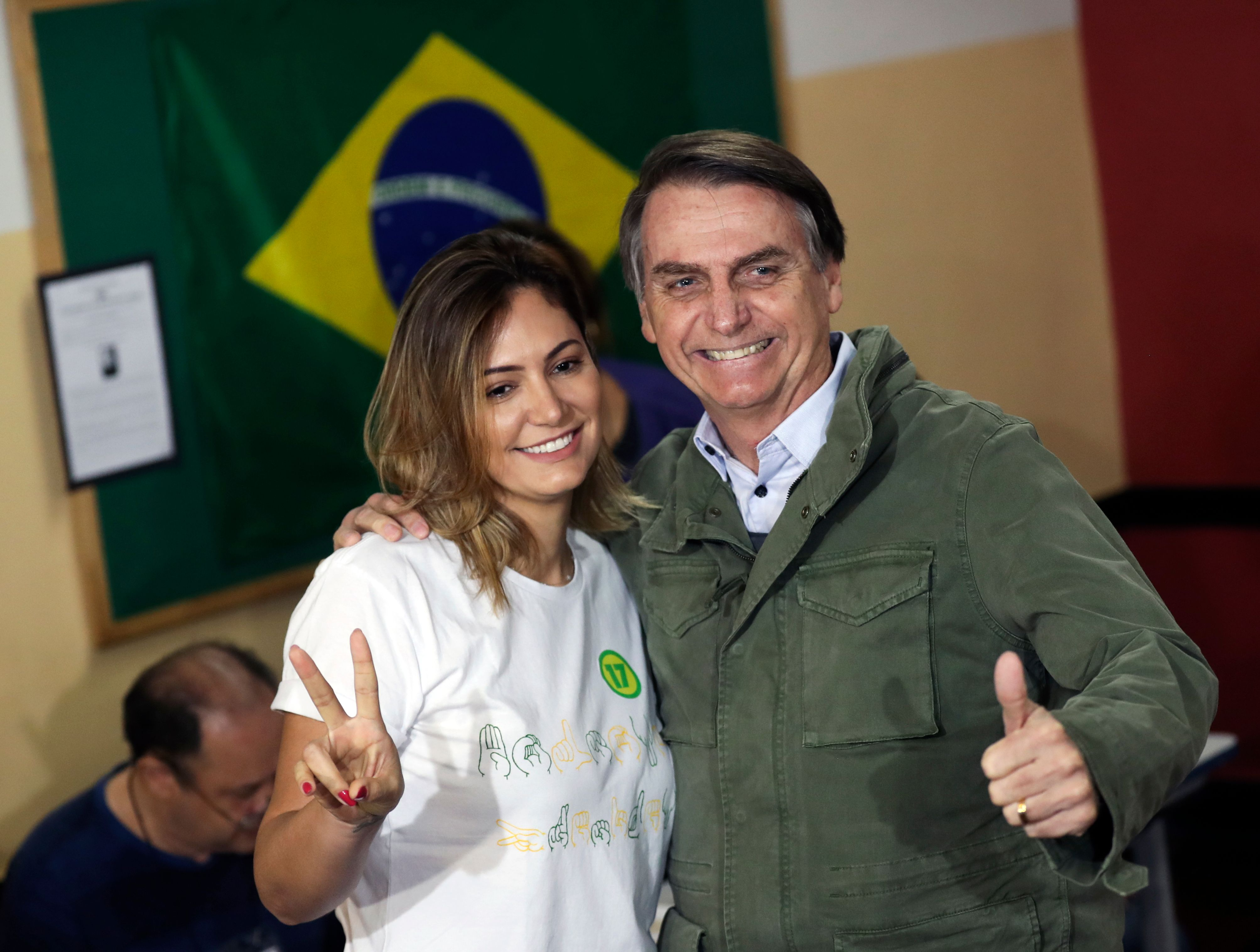 Jair Bolsonaro, far-right lawmaker and presidential candidate of the Social Liberal Party (PSL), and his wife Michelle pose as they arrive to cast their votes, in Rio de Janeiro, Brazil October 28, 2018 (Photo by RICARDO MORAES / POOL / AFP)