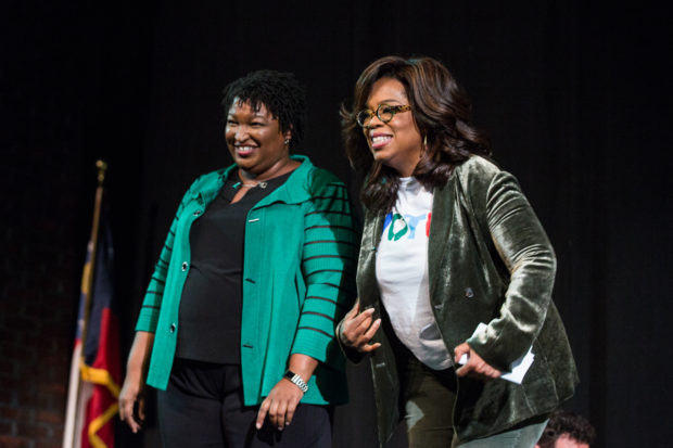 MARIETTA, GA - NOVEMBER 01: Oprah Winfrey and Georgia Democratic Gubernatorial candidate Stacey Abrams greet the audience during a town hall style event at the Cobb Civic Center on November 1, 2018 in Marietta, Georgia. Winfrey travelled to Georgia to campaign with Abrams ahead of the mid-term election. (Photo by Jessica McGowan/Getty Images)